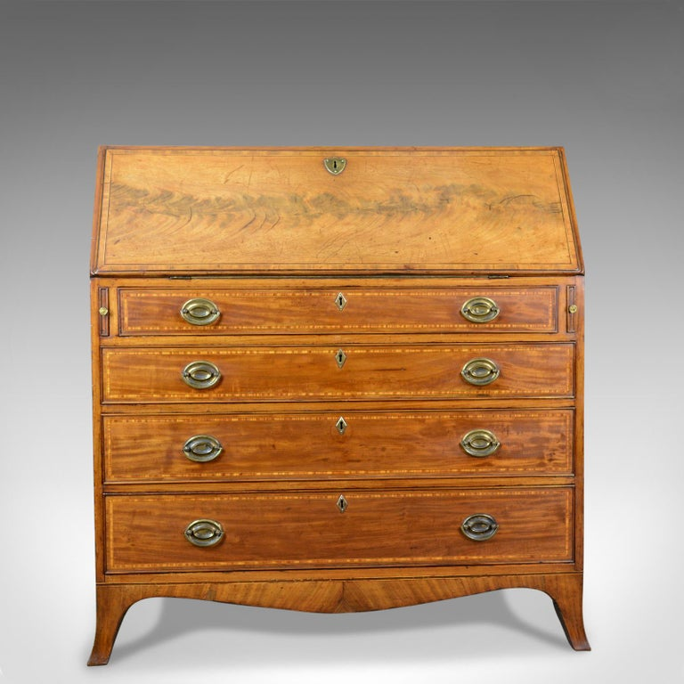 This is an antique bureau in light mahogany. An English, Georgian desk dating to the mid-18th century, circa 1770.  Quality craftsmanship in polished mahogany Good color and grain interest throughout Crossband decoration held in tramline ebony