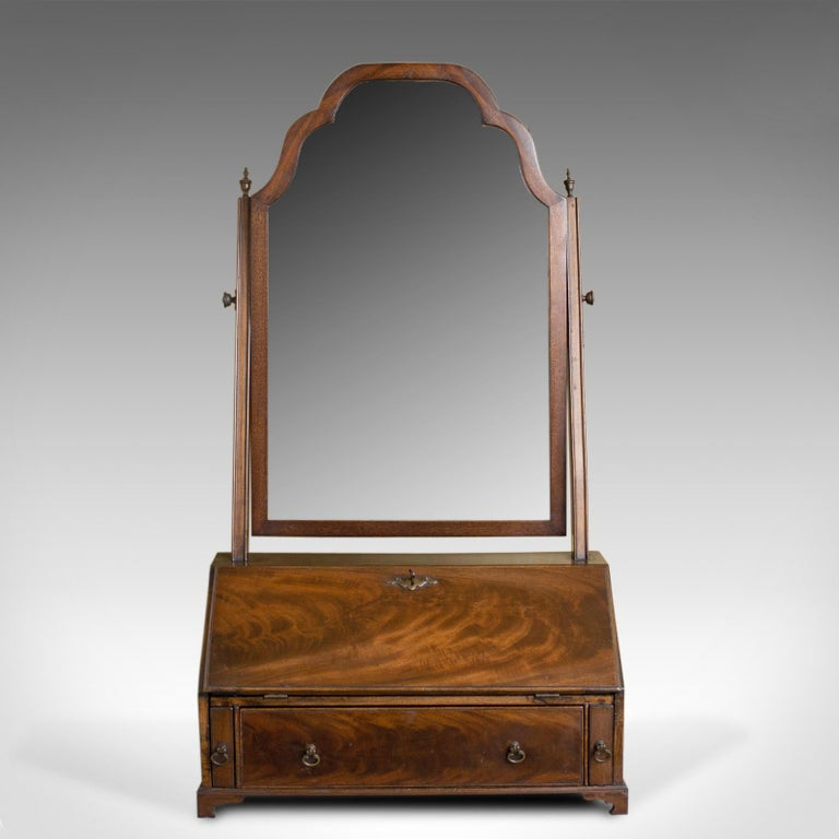 This is an antique bureau mirror, an English, Georgian revival, mahogany, toilet or vanity mirror dating to the Edwardian era circa 1910.  A delightful dressing table vanity mirror The mahogany frame displaying good color throughout The original
