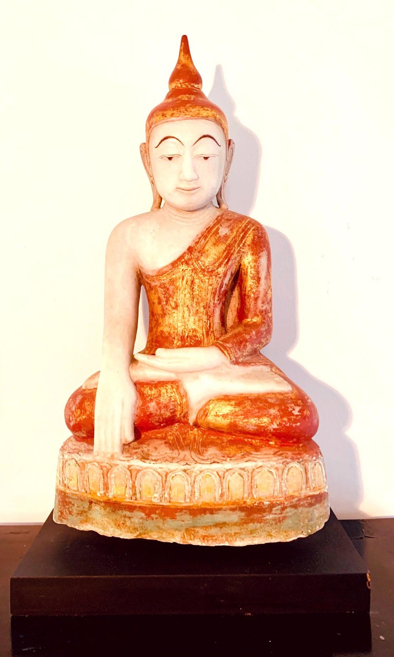 Finely carved from a solid block of white marble and decorated with red and gold pigments, this Buddha statue is depicted as seating on a lotus throne in an