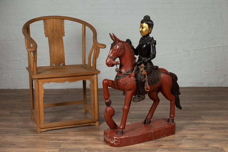 A vintage Burmese polychrome wooden statue from the mid-20th century, depicting a warrior on a horse. Born in Burma during the mid-century period, this striking carved wooden statue features a warrior sitting proudly on his brown horse. The