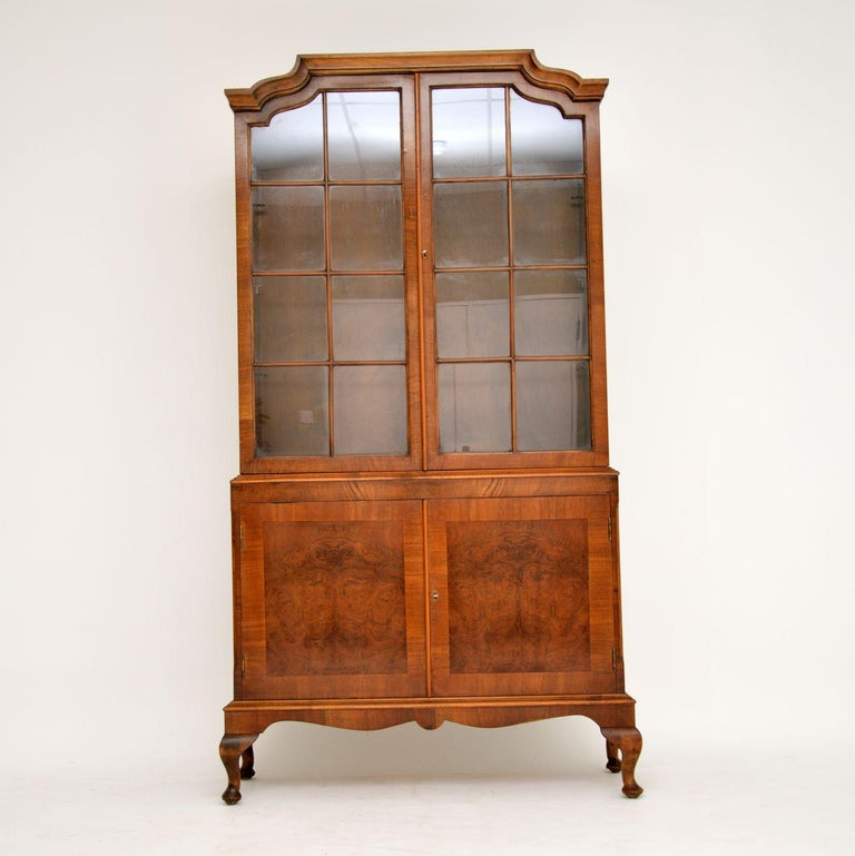 Antique two-section astral-glazed walnut bookcase with a burr walnut panelled cupboard below and sitting on Queen Anne feet. It has a shaped top and the bottom section has chamfered edges. There are adjustable shelves in the top section and a loose