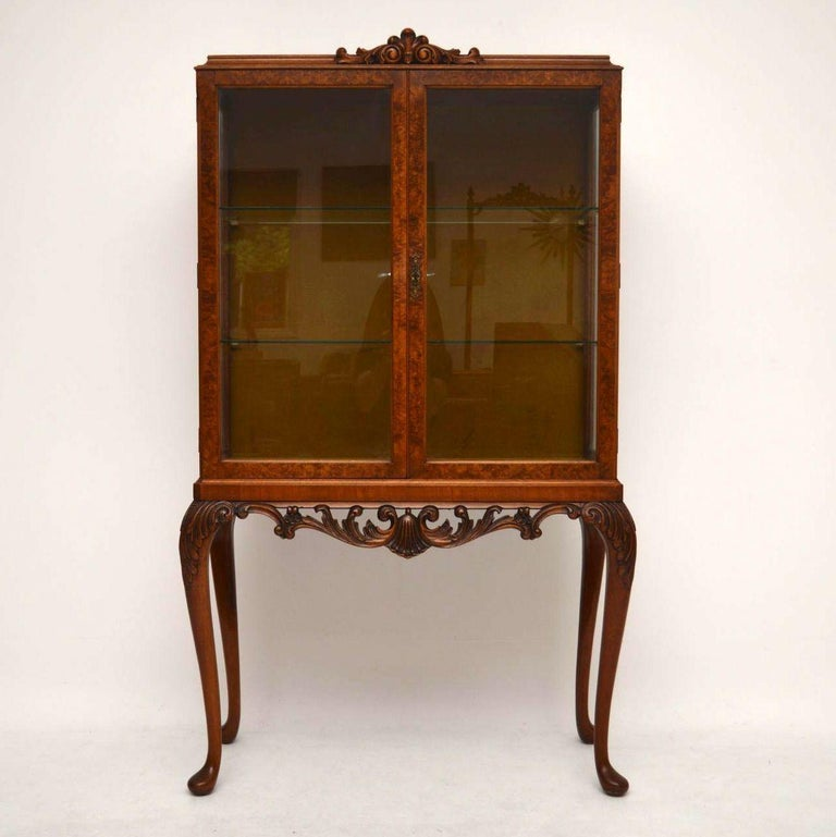 Fine quality antique walnut display cabinet in excellent condition, dating to circa 1920s period. The top section has two burr walnut glazed doors with two glass shelves inside and fabric on the back. It sits on well carved solid walnut legs with