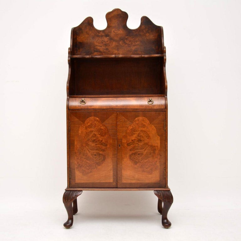 Antique burr walnut cabinet with bookshelves above the cupboards.  This is a very useful piece of furniture, which could fit in many locations in the home.  The top and the sides are beautifully shaped out and it sits on carved feet. It has a
