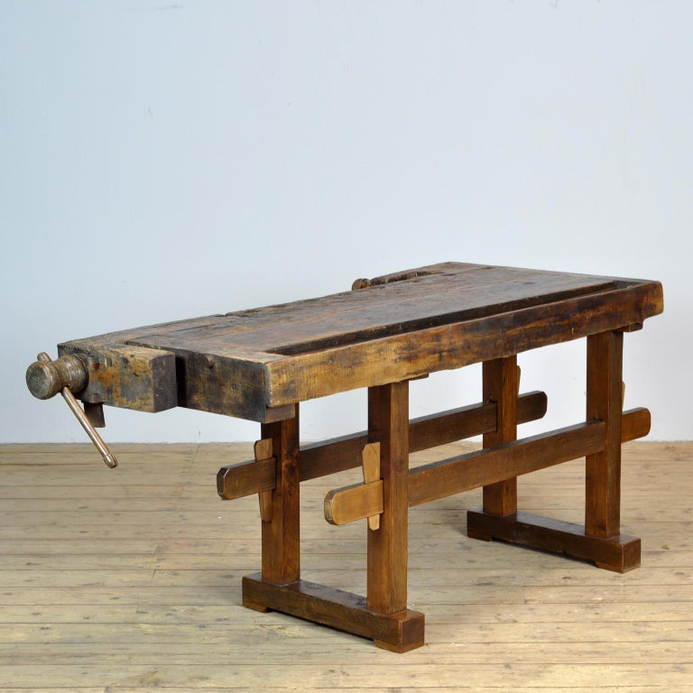 This antique workbench has two built-in wooden vices screws and a recessed tray where the carpenter would put his tools. It was manufactured around 1930. Made from oak. Beautiful patina after years of use. The workbench has been treated for