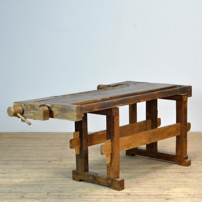 This antique workbench has two built-in wooden vices screws and a recessed tray where the carpenter would put his tools. It was manufactured around 1910. Made from oak. Beautiful patina after years of use. The workbench has been treated for