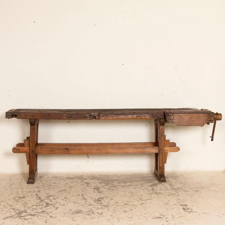 It is the years of constant use revealed in every ding and scratch that enrich the character of this carpenters' workbench from Denmark. Please examine the close up photos to appreciate the dark patina, joints and old hardware. It has one vice with