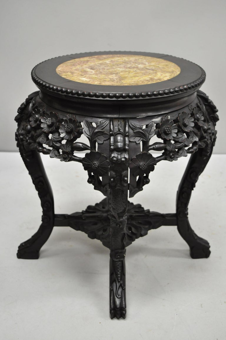 Antique Carved Hardwood Rosewood and Marble Top Chinese Pedestal Table (A). Item features inset marble top, pierce carved floral skirt, carved stretcher base, solid wood construction, finely carved details, very nice antique item. Circa Late 19th to
