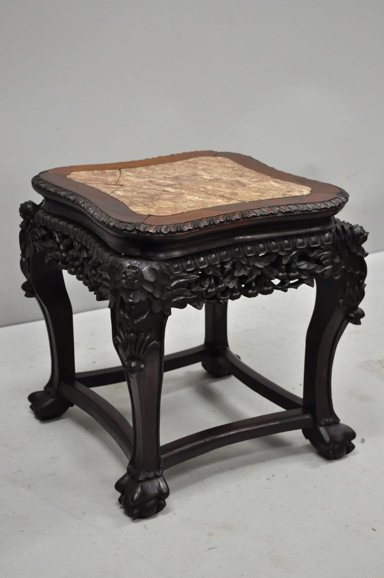 Antique carved hardwood rosewood and marble-top Chinese pedestal table (H). Item features inset marble top, pierce carved floral skirt, carved stretcher base, solid wood construction, finely carved details, very nice antique item, circa late