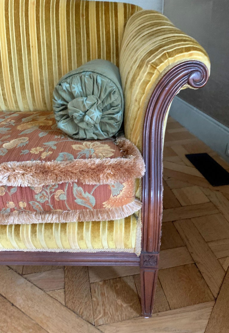 Antique camelback loveseat with a carved mahogany frame and newer upholstery in gold velvet stripes and coordinating floral fabric. Includes two bolster pillows.