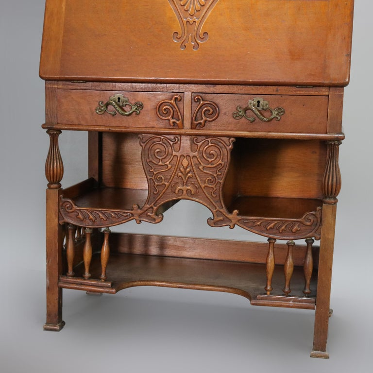 An antique RJ Horner School Cowboy desk offers oak construction with gallery having carved scroll rail over mirrored upper with central drawer and flanking cabinets over slant front desk opening to writing surface and pigeon holes surmounting lower