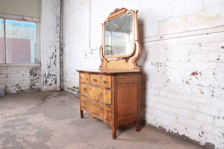 An exceptional antique carved tiger oak dresser with mirror