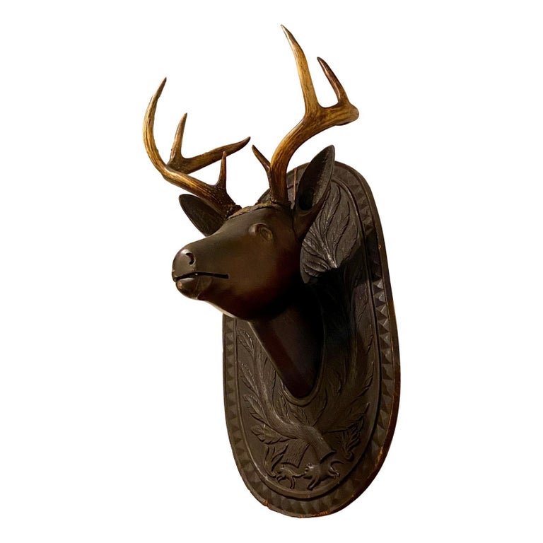 A late 19th century American Arts & Crafts / Black Forest style carved wood deer head the real antlers. The backplate is hand-carved with a branch and leaf motif and a hunting dog chasing a fox.  Measurements: Height: 24