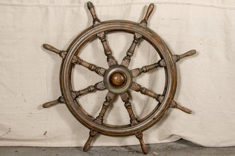 Entirely of carved wood with turned spokes. One grip with a metal cap.   Condition: Good condition with expected signs of use and wear including well-worn overall with a few cracks as expected with use out at sea and the wheel presents very well.
