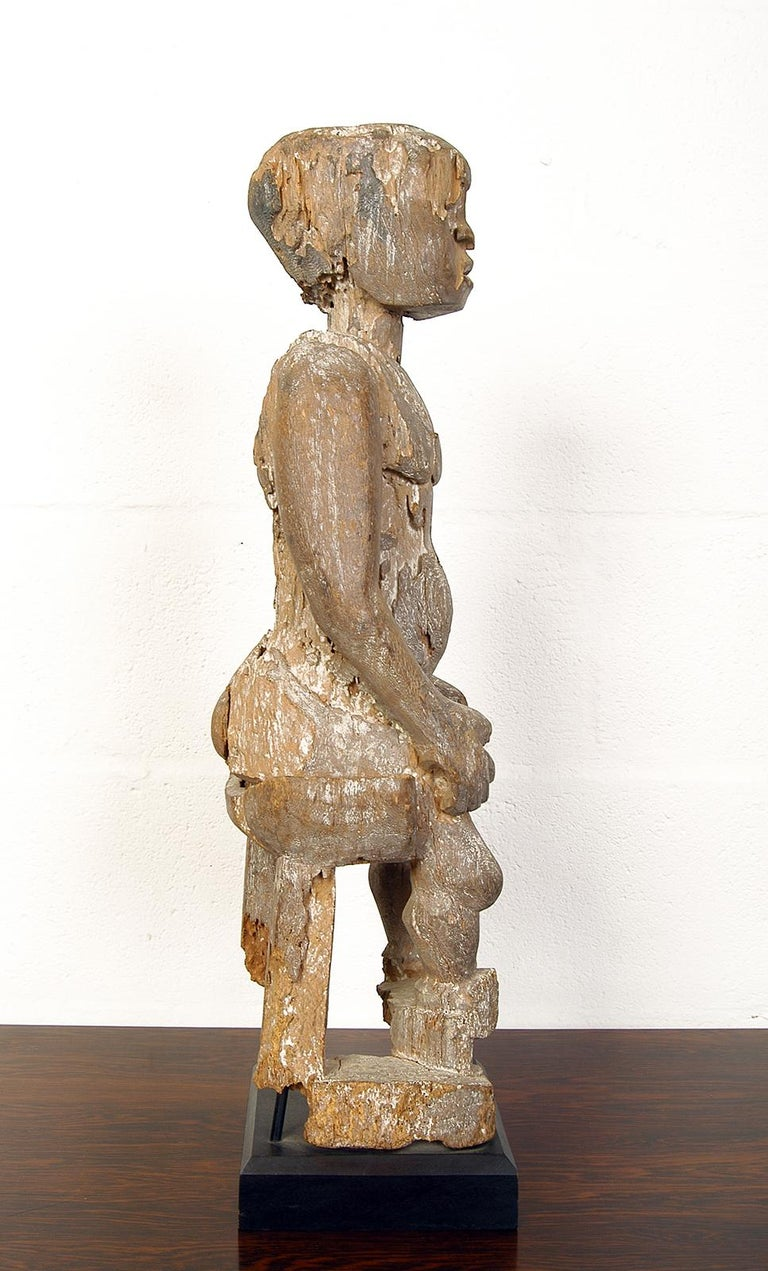 A wonderful ancient carved wooden fragment depicting a seated man with the most amazing patina – carefully mounted on a later ebonised wooden plinth.  Standing 69cm tall, the base 17.5cm square.
