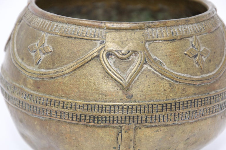 A medium sized antique cast brass measuring bowl from northern India.  High relief casting, bundled rope maker's mark on the bottom. Bronze rice-measuring bowl from Eastern India. Circa 1900 collectible antique tribal bowl handmade using the lost