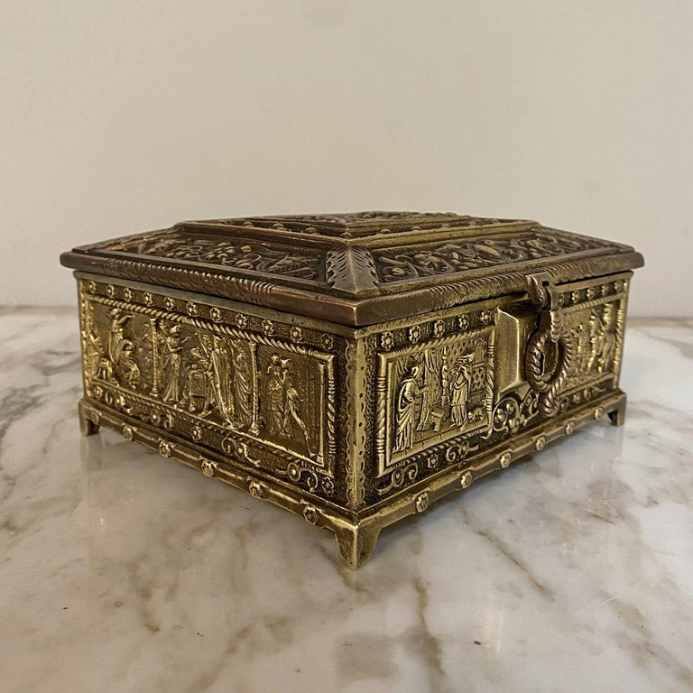 Antique cast bronze Jewelry Box features astounding detail across every facade! The top is a flattened pyramid shape, with a romantic scene portrayed, surrounded by heraldic crests, foliates, satyrs and hippogryffs. On each side appear medieval