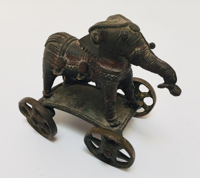 Antique cast bronze elephant temple toy on wheels from India. This beautifully patinated brass temple elephant on wheels is from Bhundi in Rajasthan. This would look perfect on a desk and is heavy enough to use as a paperweight 19th century Hindu
