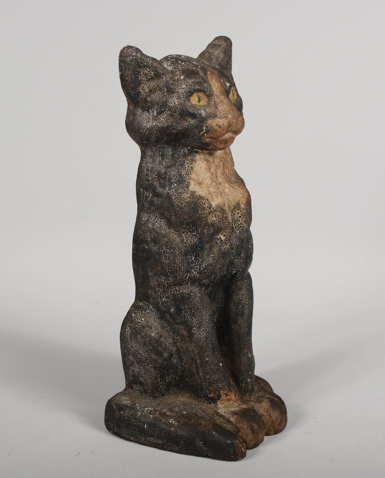 Early 20th century cast iron door stop. This was made by National Foundry, Whitman, Mass. This cat has great patina with original paint with heavy crazing.