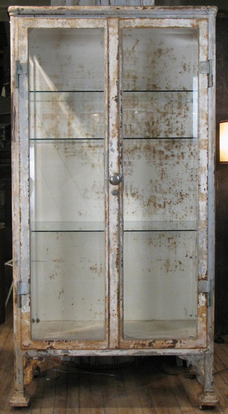 A very handsome antique 1930s apothecary or display cabinet with a cast iron and steel frame, and beveled glass doors and side panels. With glass shelves. In its original distressed white finish. One of the most substantial apothecary cabinets from
