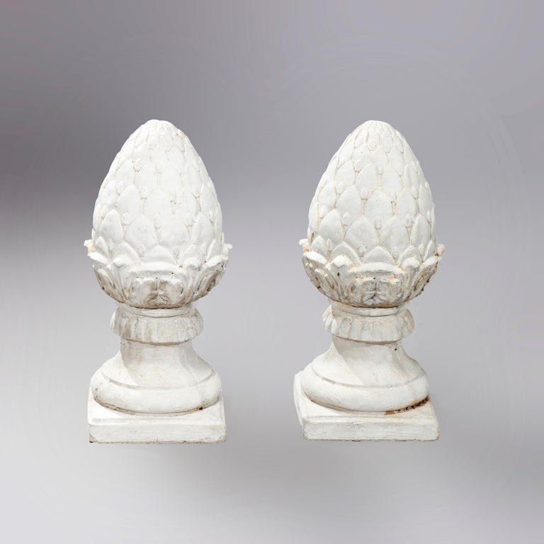 A pair of antique garden finials offer cast stone construction in acorn or artichoke form seated on square bases, 20th century  Measures: 19