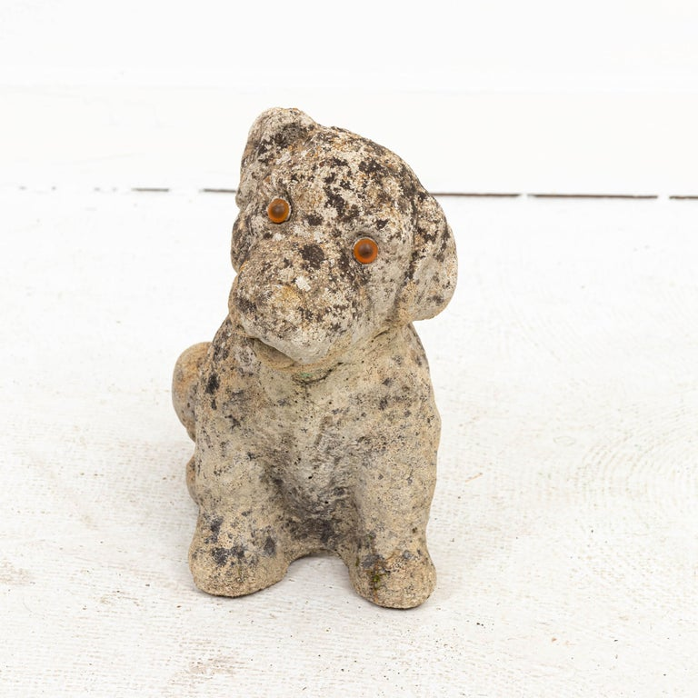 Unique cast stone garden statue of a puppy with striking amber eyes. Made in England circa early 1900s. Original garden patina with moss covering adds to its character.