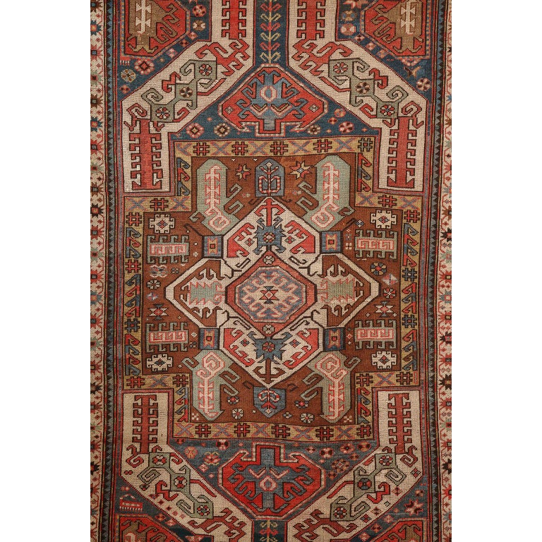 This antique Caucasian carpet in pure handspun wool and vegetable dyes circa 1880 features a multi-layered central medallion with multiple borders and an overall geometric design and field. Its striking composition is well proportioned and further