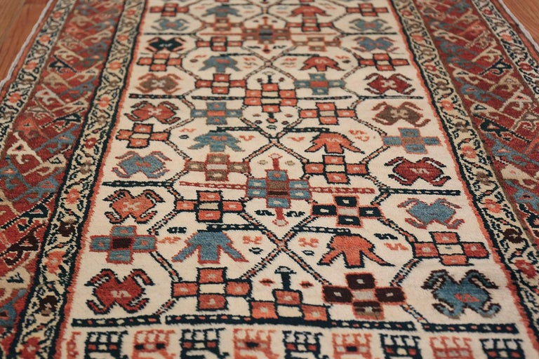 Antique Caucasian Tribal long and narrow Kazak runner, origin: The Caucasus, Woven circa 1900 - A thin border of orange and natural brown frames the rich cream background of this antique Kazakh rug. A deceptively simple pattern comprised of orange,