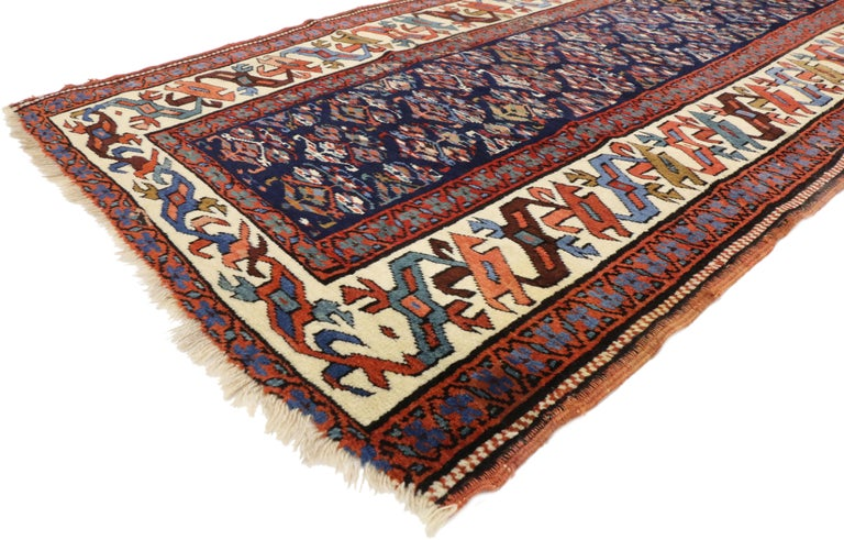 73257, antique Caucasian Kazak Tribal runner, hallway runner. This hand knotted wool antique Caucasian Kazak tribal runner features an all-over geometric pattern of tulip palmettes on an ink blue field. The tribal Kazak runner is framed by a cream
