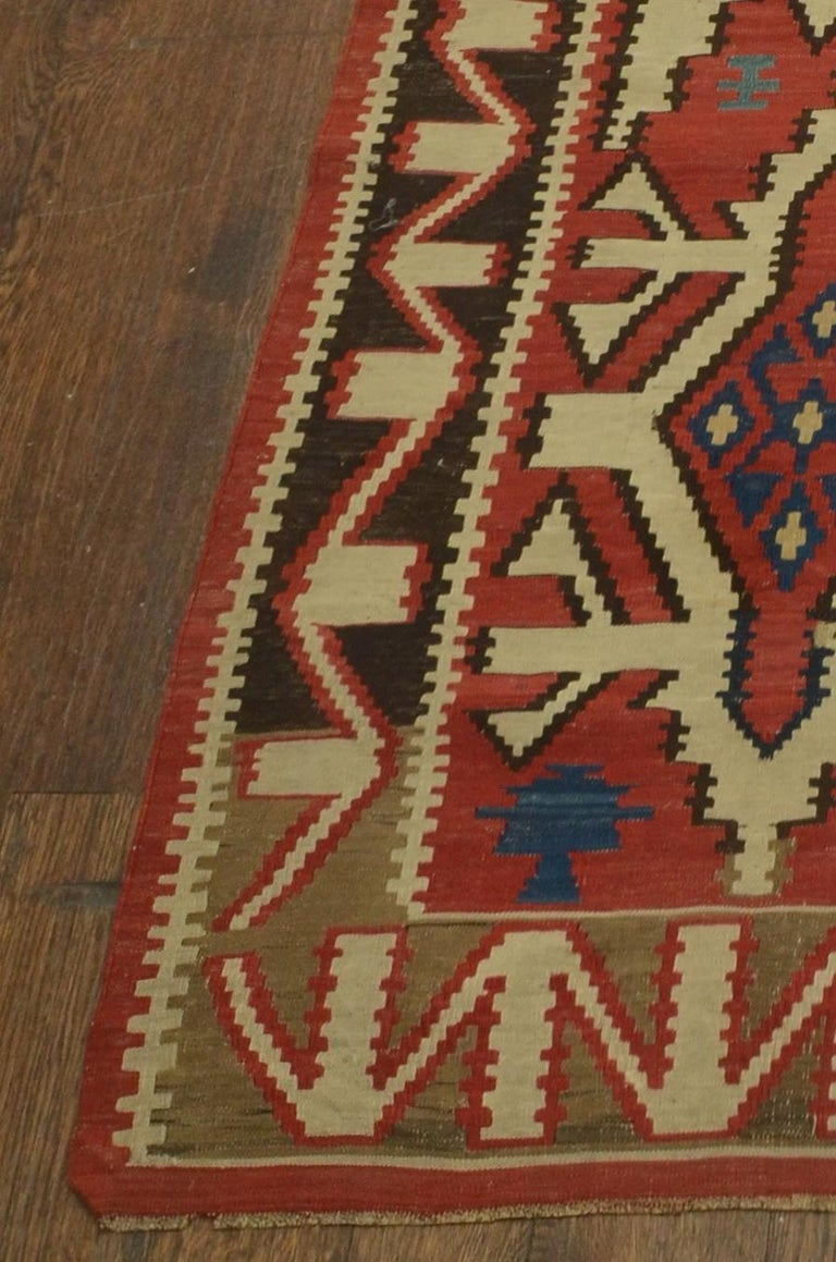 Classic kuba kilm in rich vegetable design colors of terracotta red background. Palmettes in various sizes float with blue, ivory and brown tones. The meandering border design offers a perfect frame for this Classic Caucasian Kilim.