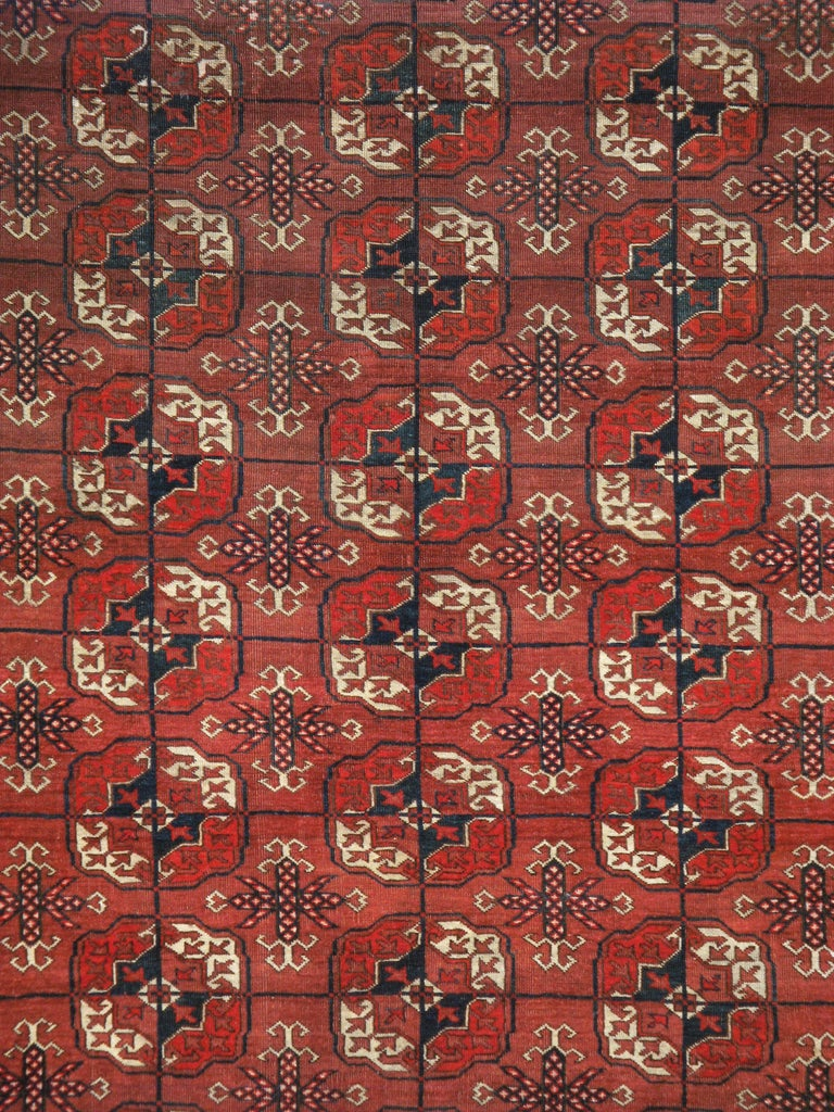An antique Central Asian Tekke rug. From the most important Turkmen weaving tribe in Turkmenistan, this blood red nomadic rug displays five columns of eleven characteristic gul (flower) medallions within a color matched border of rayed octagons