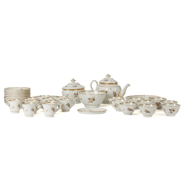 A stunning and extensive antique Chamberlain Worcester porcelain part tea set hand painted with floral designs highlighted with gilding on a white fluted body. The set comprises of a lidded teapot, a lidded sugar bowl, teapot stand, slop bowl, two