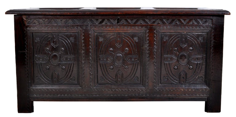 Antique Charles II carved oak coffer / chest / trunk, circa 1670. The coffer having a three-paneled top which corresponds to the three panels to the front, the front carved with oval geometric devices and a chevroned gallery above. The coffer being