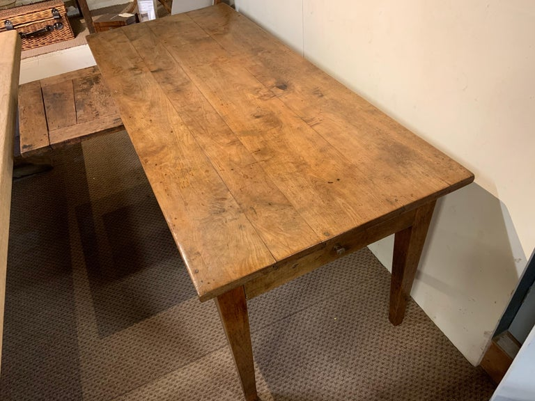 19th century pale cherry with gorgeous four plank top. The table sits on sturdy tapered legs, with one drawer on the end. The table has a great side bread slide. The gorgeous-looking table stands really well with excellent proportions.