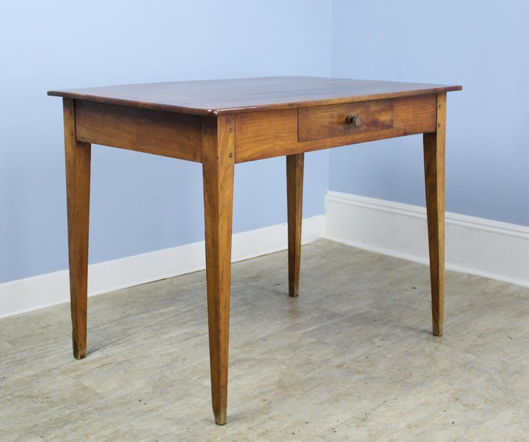 A graceful French antique writing table in vibrant cherry. Elegant tapered legs and a comfortable 24