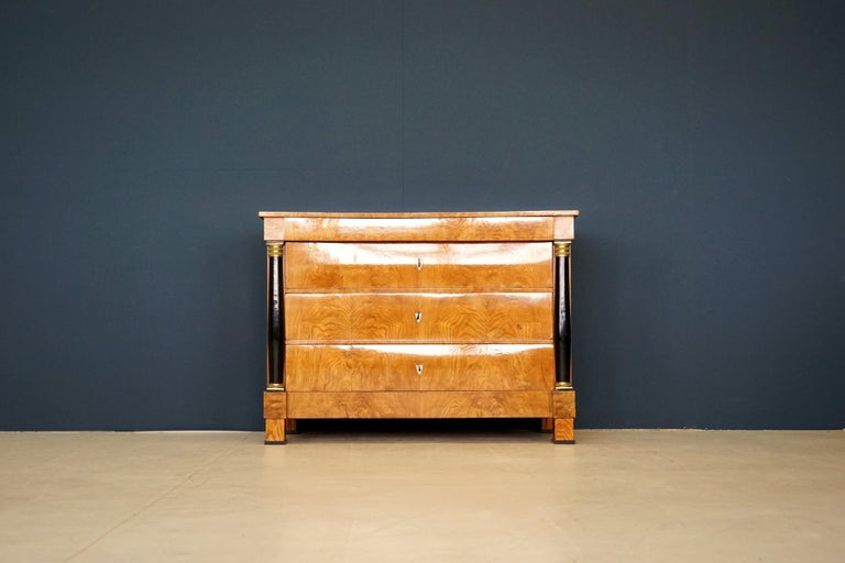 Antique chest of drawers, circa 1815. German Biedermeier. Ash on solid softwood corpus. Restored. Antique chest of drawers with three large drawers and a narrow head drawer. Ash veneered on solid softwood body, with gilded capitals. Extremely rare