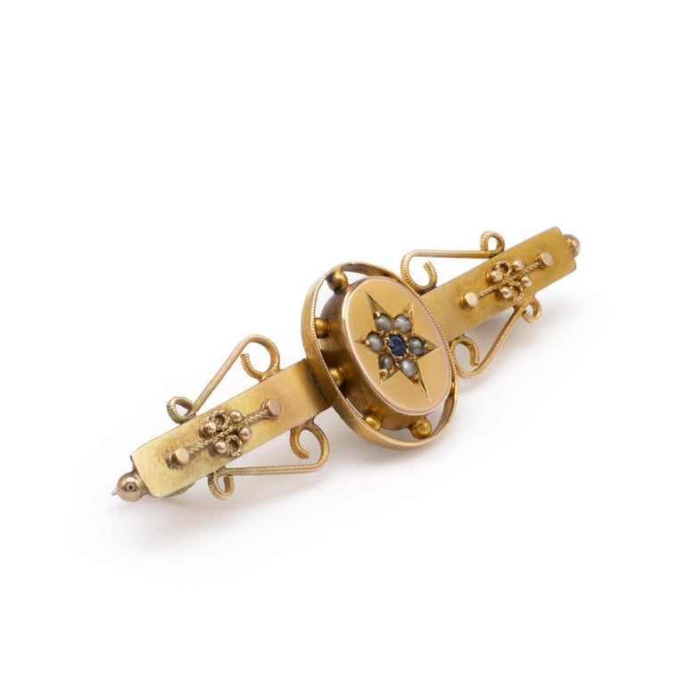 This Edwardian antique gold bar brooch pin with sapphire and seed pearl is hallmarked and dated Chester 1904.  The brooch displays a sapphire and seed pearls set into a star shape on an oval plinth with gold ball decorative edge. The bars are