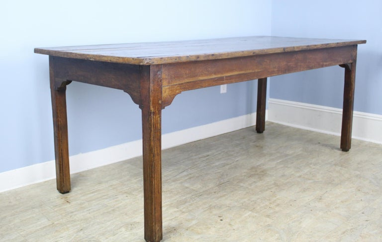 A charming French chestnut farm table with a decorative wood trimmed edge. The mellow chestnut has wonderful color and patina, highlighted by naturalistic grain lines. Sweetly carved corners on the apron add an additional design note, as do the