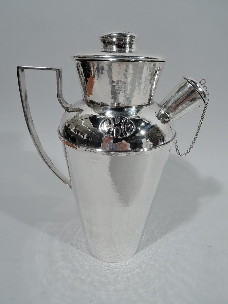 Craftsman sterling silver cocktail shaker. Made by Lebolt in Chicago, circa 1920. Tapering and wide-bodied bowl and neck, and stubby spout with chained and cork-lined cap. Cover flat and cork-lined with button finial. High-looping scroll handle. All