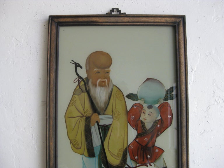 Antique Chinese hand painted reverse painting on glass. Features an Immortal and a boy holding a peach (A symbol of all things good). Great detail and color. Painting displays well and is in its original frame. In overall very nice original