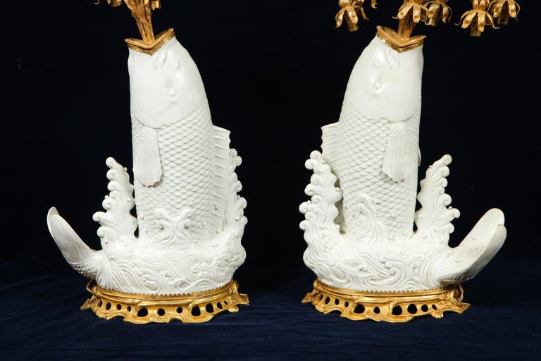 A very fine and quite unusual pair of antique Chinese fish-form Blanc de Chine porcelain vases mounted with beautiful antique French Louis XV style doré bronze fountain-form overflowing water fall eight-arm candelabra lamps. The porcelain; Chinese,