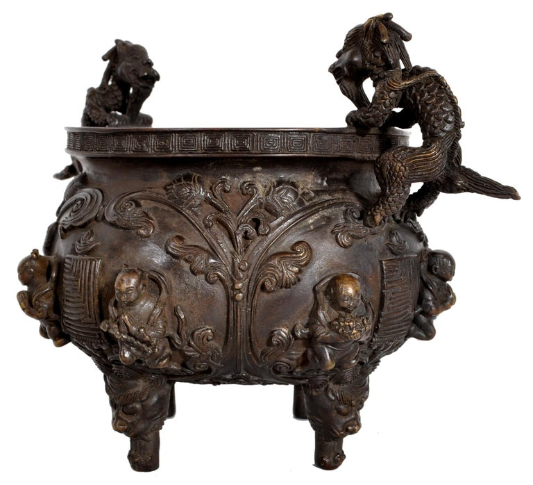 A fine antique Chinese bronze Buddhistic Qing dynasty dragon censer, circa 1800. The censer modeled in high relief with twin handles finely cast as dragons, the body of the censer having floral decoration and praying Buddhistic figures. The base of