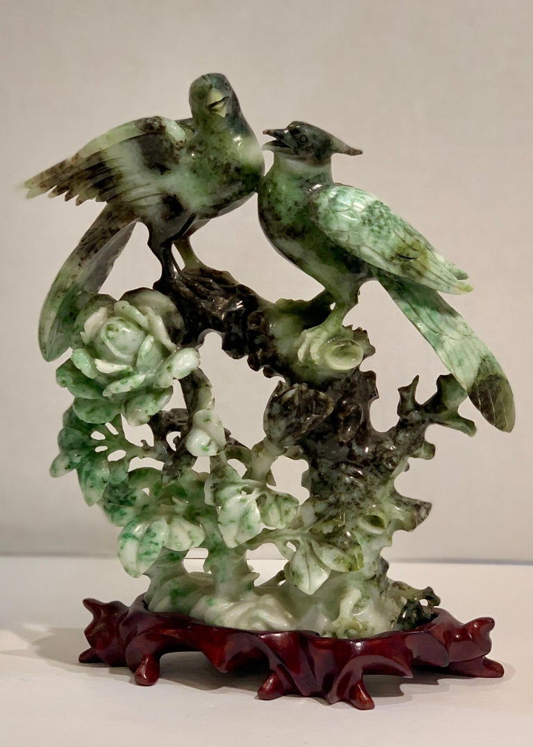 Intricately hand carved from a single block of richly variegated green and white stone, this incredibly detailed Chinese sculpture of two birds on a branch above flowering, leafy roses is a work of art. The mottled green and white stone enhance the