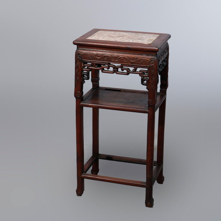 An antique Chinese plant stand offers rosewood construction with inset marble top over frame with foliate carved and pierced skirt over lower display shelf and having stylized claw and ball feet, 19th century  Measures: 32.75
