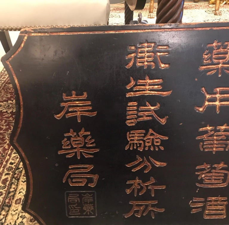 Unique hand carved wood trade sign from China, 1890s. The sign with hand carved Chinese lettering with gilt highlights. The black background with a gilt border.