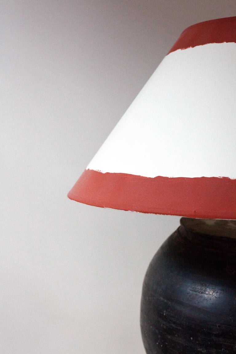 An earthenware ceramic jar later made into a lamp with E26 socket and Euro plug. A custom hand painted shade has been added consistent with the vernacular of the antique piece.