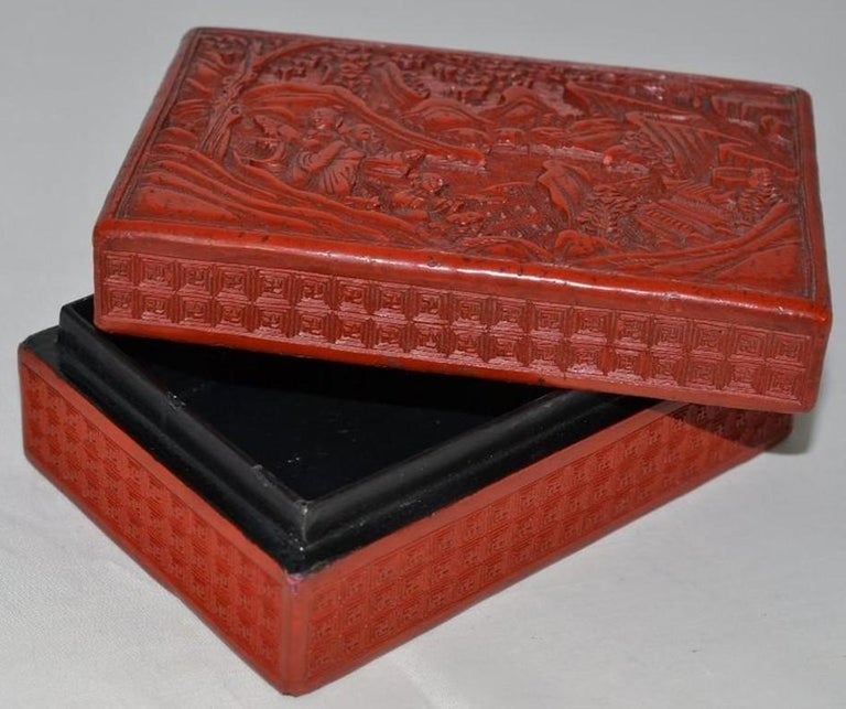 Red lacquer box with the lid to depict a scholar and children at play within a mountainous garden setting, the exterior sides covered in repeating geometric patterns. 14.5 cm wide.
