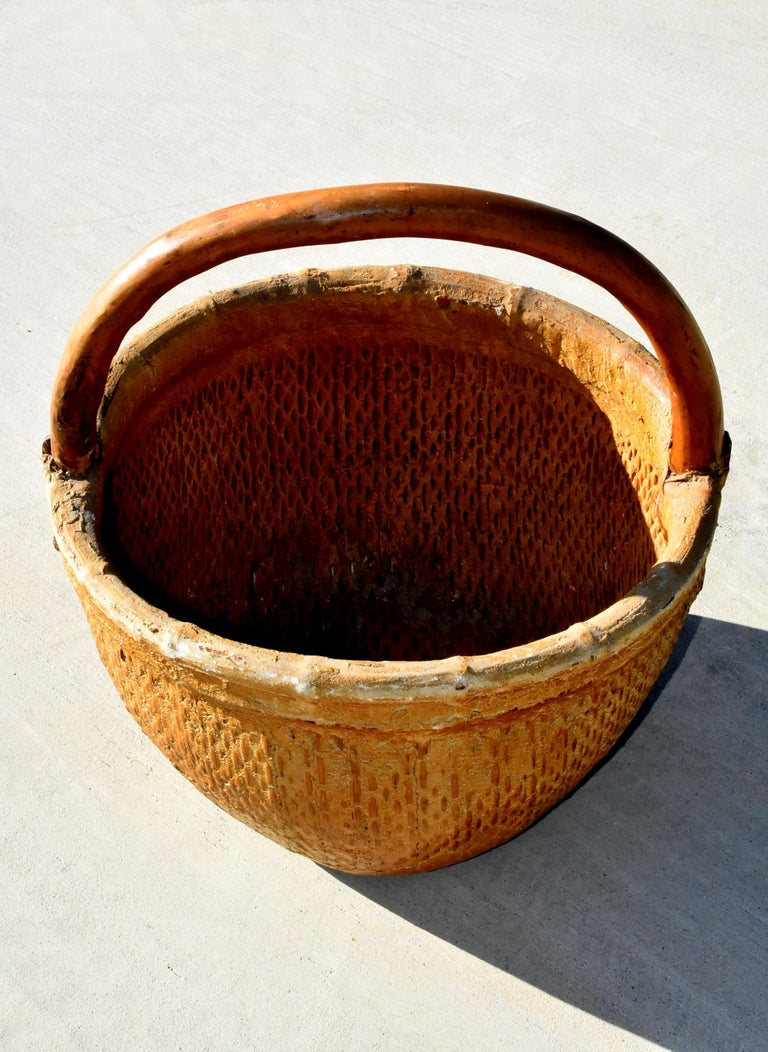 A wonderful antique basket with a tree branch handle and iron bracket enforcement. The willow basket is tightly woven and sealed in clay and fabric. This is a large basket that can be used for many purposes. Great organic, country charm. Handmade.