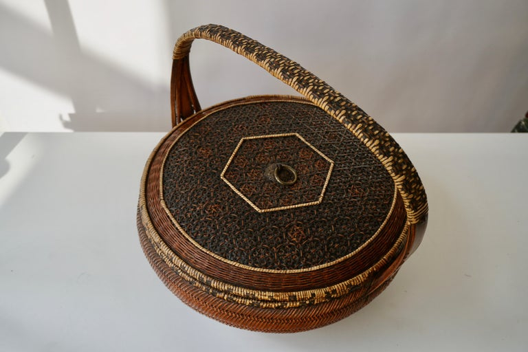 A Chinese 19th century brown basket handwoven with rattan and bamboo. This circular basket features a squat handle. The middle part is covered with a colored rattan. The base of this basket displays brown and black rattan geometrical patterns, while