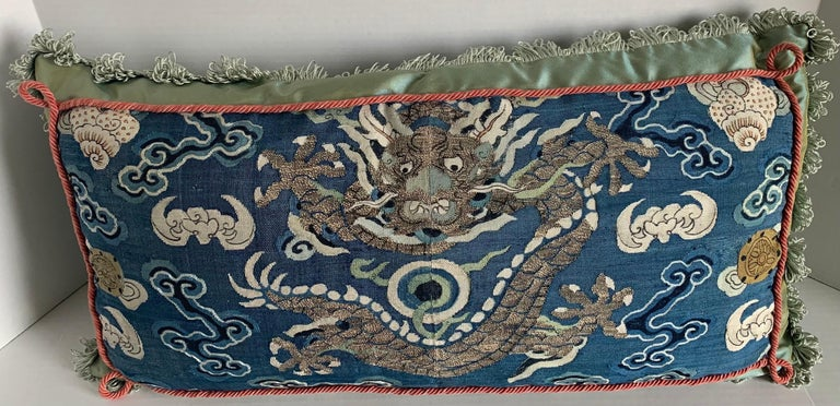 Antique Chinese embroidered textile made into a custom lumbar pillow. Antique blue woven silk textile featuring center dragon motif.  Pillow is made of Scalamandre iridescent celadon green silk with brushed fringe and gimp trim.  Sewn shut style,