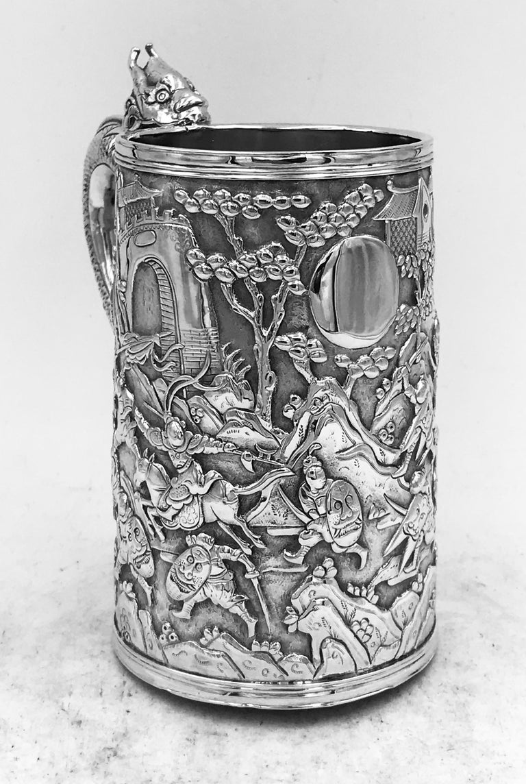 A Chinese silver mug of typical double-skinned construction, decorated with battle scenes against a matt background. It has a vacant cartouche and a dragon handle. Marked with HC, for Hung Chong ???Hung Chong was a retailer based in Canton from